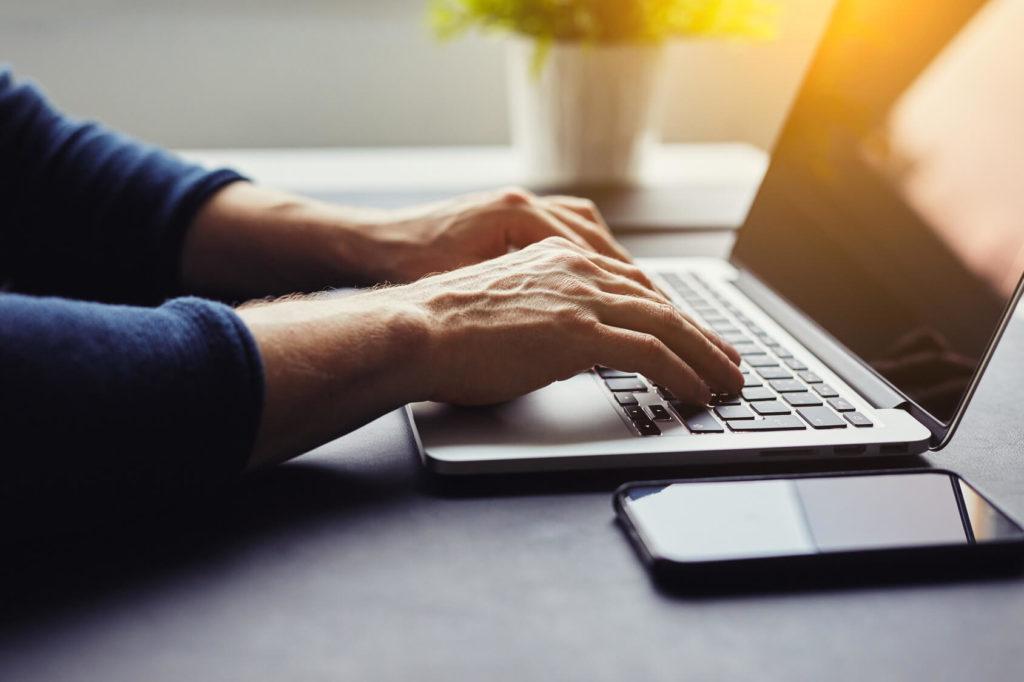 Mann tippt auf Laptop-Tastatur
