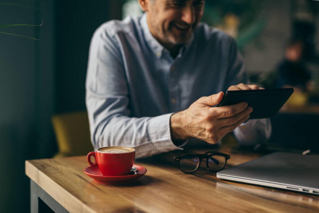 Mann liest Blogartikel auf Smartphone