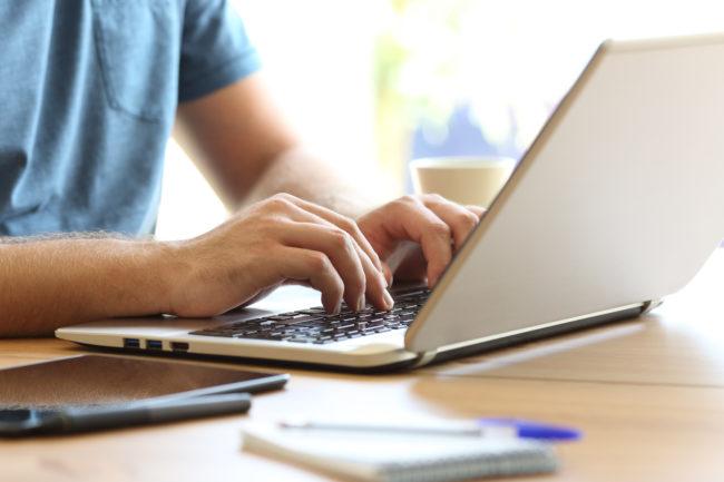 Mann tippt am Laptop auf Schreibtisch
